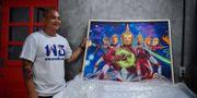 Konsthandlaren Pakorn Porncheewangkul med en av de kontroversiella Buddha-tavlorna. LILLIAN SUWANRUMPHA / AFP