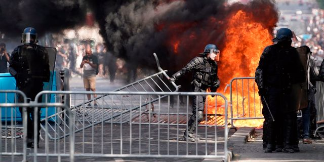 Demonstranter välte barriärer och satte eld på soptunnor. KENZO TRIBOUILLARD / AFP