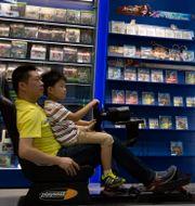 En försäljare hjälper ett barn i en gamingaffär i Peking. Ng Han Guan / TT NYHETSBYRÅN