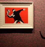 Motivet med den maskerade mannen som kastar blomsterkvasten är ett av Banksys mest kända. Här på en utställning i Rom.  Alessandra Tarantino / TT NYHETSBYRÅN