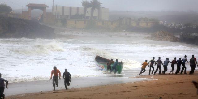 Fiskare försöker dra in en båt till land i Gujarat.  Ajit Solanki / TT NYHETSBYRÅN