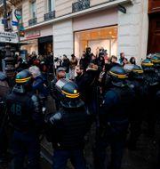 Strejkande anställda hos kollektivtrafiken omringas av kravallpolis i Paris. FRANCOIS GUILLOT / AFP