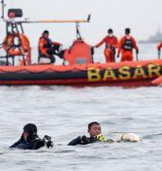 Dykare tar upp vrakdelar från det störtade flygplanet från havet utanför Jakarta.  Achmad Ibrahim / TT NYHETSBYRÅN