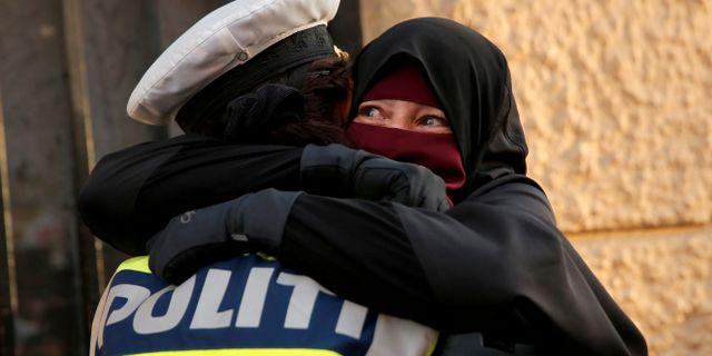 Ayah kramar om en kvinnlig polis under demonstrationen tidigare i somras. ANDREW KELLY / TT NYHETSBYRÅN