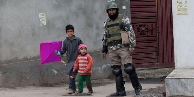 Barn går förbi en soldat i den indisk-kontrollerade delen av Kashmir.  Dar Yasin / TT NYHETSBYRÅN/ NTB Scanpix