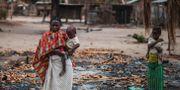 En kvinna med sitt barn i byn Aldeia da Paz i Tanzanias Cabo Delgado-region som attackerats av islamister. MARCO LONGARI / AFP