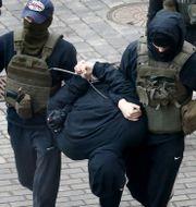 Belarusisk polis griper en demonstrant.  TT NYHETSBYRÅN