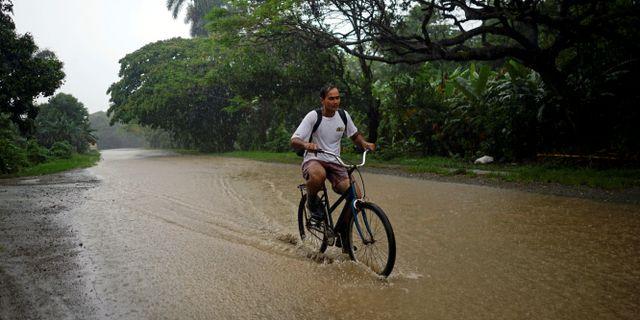 En man cyklar på en översvämmad gata på Kuba, som stormen Alberto passerade i helgen.  ALEXANDRE MENEGHINI / TT NYHETSBYRÅN