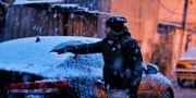 En man tar bort snö från vindrutan på sin bil i Bagdad. Hadi Mizban / TT NYHETSBYRÅN