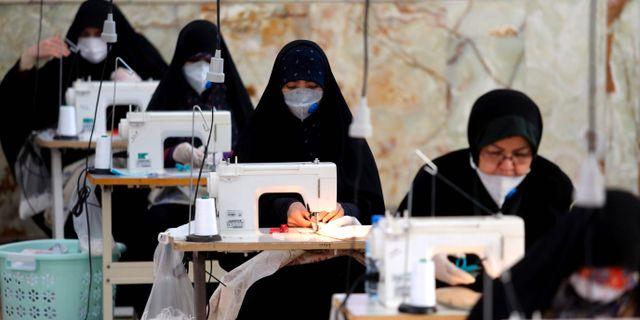 Kvinnor i Iran som tillverkar munskydd. ATTA KENARE / TT NYHETSBYRÅN
