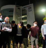 Apple Dailys reportrar bugar inför tidningens supportrar utanför högkvarterat i Hongkong på torsdagen.  Kin Cheung / TT NYHETSBYRÅN