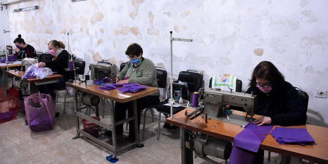 Hjälparbetare i Aleppo syr skyddsmasker.  - / TT NYHETSBYRÅN