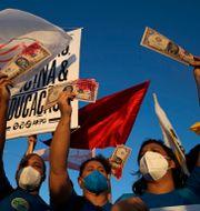 Demonstranterna höll upp falska dollarsedlar. Den röda färgen symboliserar blod från covidoffer.  Eraldo Peres / TT NYHETSBYRÅN