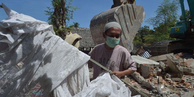 Arkivbild från 12 augusti. En man räddar föremål ur ett rasat hus efter den tidigare jordbävningen.  ADEK BERRY / AFP