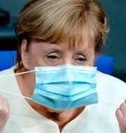 Bild från dagen. Angela Merkel sätter på sig ett munskydd i Bundesdagen. Kay Nietfeld / TT NYHETSBYRÅN