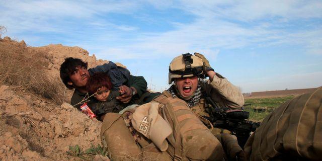 Amerikansk soldat och afghansk civilbefolkning under talibansk attack. Arkivbild. Goran Tomasevic / TT NYHETSBYRÅN