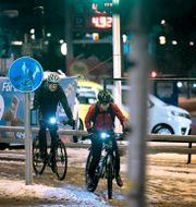 Två män på cykel i blötsnö. Janerik Henriksson/TT / TT NYHETSBYRÅN