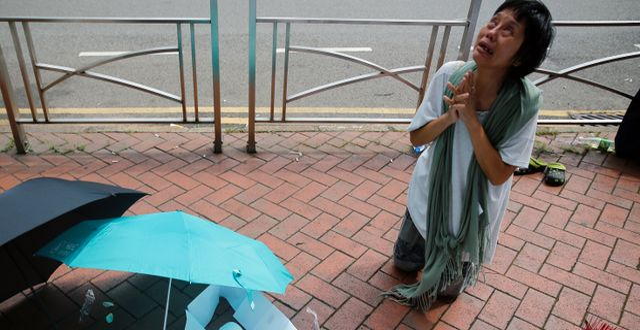 En kvinna sörjer en man som föll ner från en byggnad i samband med protesterna.  THOMAS PETER / TT NYHETSBYRÅN