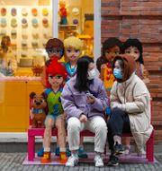 Två kvinnor med munskydd utanför en Lego-butik i Kina i våras.  Shen Bohan / TT NYHETSBYRÅN