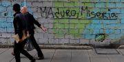 """Illustrationsbild: Två män går förbi en tegelvägg med grafittitexten """"Maduro, misär"""" i Caracas, Venezuela.  MARCO BELLO / TT NYHETSBYRÅN"""