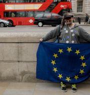 En demonstrant för EU-medlemskap håller en EU-flagga nära Downing Street i London. Matt Dunham / TT / NTB Scanpix