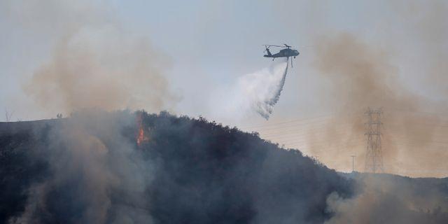 Helikoptrarna arbetar med att vattenbomba bränderna från luften Ringo H.W. Chiu / TT NYHETSBYRÅN