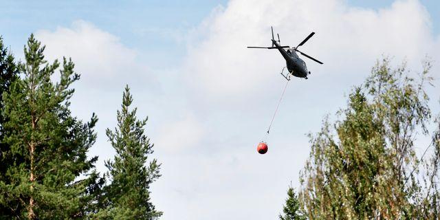 En helikopter vattenbombar de branddrabbade området runt Färila i Hälsingland. Arkivbild. Erik Simander/TT / TT NYHETSBYRÅN