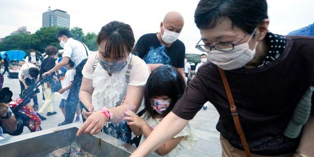 En barnfamilj tänder rökelse på årsdagen av atombomben i Hiroshima. Eugene Hoshiko / TT NYHETSBYRÅN
