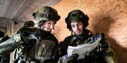 En kvinnlig soldat (tv) i full stridsutrustning under övning i markstrid i stadsmiljö. Pontus Lundahl/TT / TT NYHETSBYRÅN