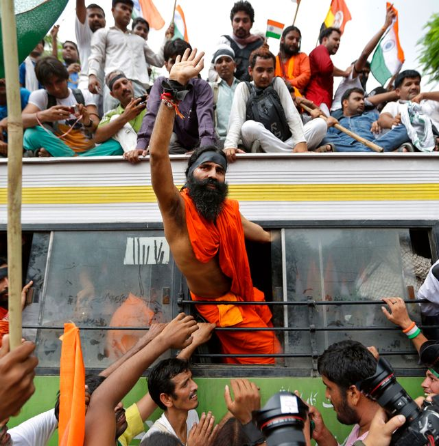 Indian yoga guru Swami Ramdev waves out of the window of a bus in New Delhi, India, Monday, Aug. 13, 2012. Saurabh Das / TT NYHETSBYRÅN