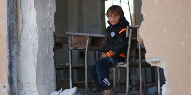 En pojke sitter i ett förstört klassrum i Idlib, Syrien 2016. Uncredited / TT NYHETSBYRÅN