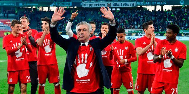Tränaren Carlo Ancelotti jublar tillsammans med laget. JOHN MACDOUGALL / AFP