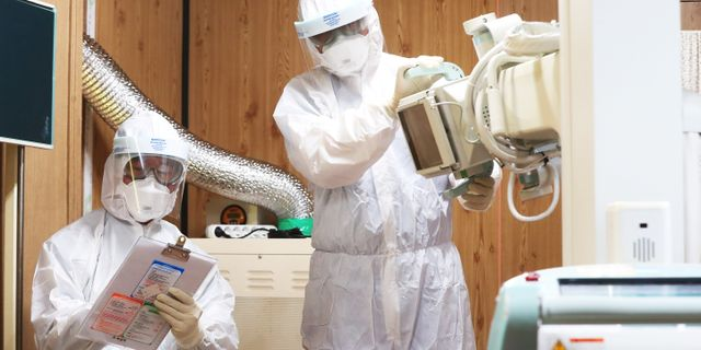 Medicinsk personal i Sydkorea förbereder ett undersökningsrum för misstänkt smittade. STRINGER / TT NYHETSBYRÅN