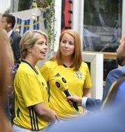 Annie Lööf (C) och Annika Strandhäll (S) i landslagströjor efter VM-segern mot Schweiz Vilhelm Stokstad/TT / TT NYHETSBYRÅN