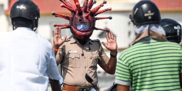 """Indiske polisen Rajesh Babu bär """"coronahjälm"""" för att sprida medvetenheten om coronaviruset. ARUN SANKAR / TT NYHETSBYRÅN"""