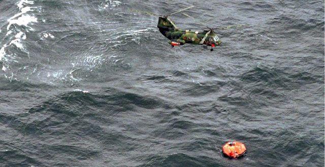 En helikopter cirkulerar ovanför en livbåt som slagit runt. KUSTBEVAKNINGEN / TT / TT NYHETSBYRÅN