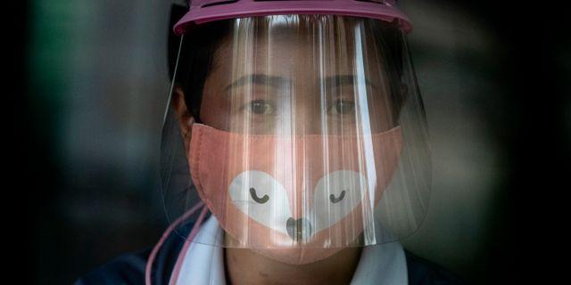 Kvinna med munskydd och visir i Thailand. Gemunu Amarasinghe / TT NYHETSBYRÅN