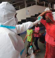 Hälsovårpersonal kontrollerar temperatur i Mumbai. Rafiq Maqbool / TT NYHETSBYRÅN
