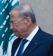 En kritiker till regeringen bränner en bild på president Michel Aoun. TT