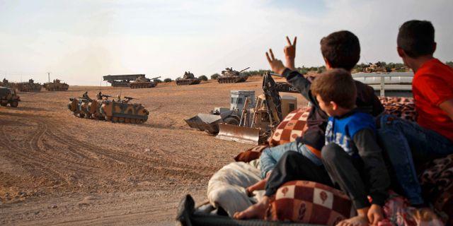 Civila gör segertecken till turkiska styrkor i Syrien.  AAREF WATAD / AFP