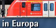 """Ett pendeltåg med namnet """"Wuhan China"""" på centralstationen i Essen i Tyskland. I förgrunden syns en skylt var hela text lyder """"I mitten av Europa"""". Martin Meissner / TT NYHETSBYRÅN"""