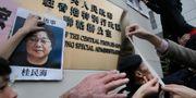 Demonstranter sätter upp ett foto av  Gui Minhai vid en demonstration i Hongkong.  Vincent Yu / TT NYHETSBYRÅN