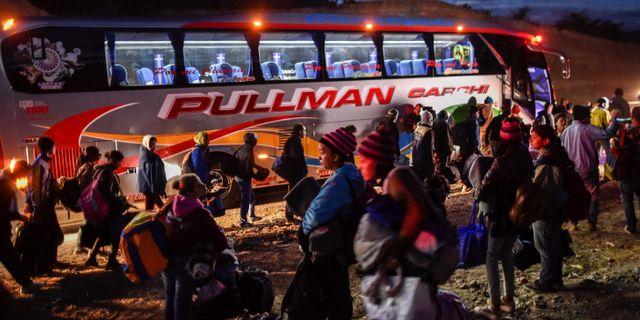Venezolanska migranter vid en buss som ska ta dem till gränsen mellan Ecuador och Peru.  LUIS ROBAYO / AFP