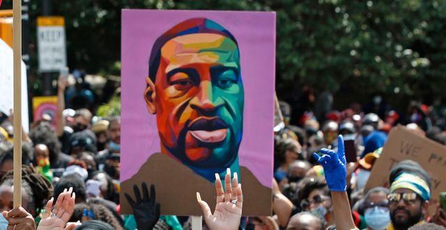 Demonstranter med ett porträtt på George Floyd. Kathy Willens / TT NYHETSBYRÅN