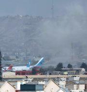 Rök stiger efter en av de dödliga explosionerna vid Kabuls flygplats på torsdagen.  Wali Sabawoon / TT NYHETSBYRÅN