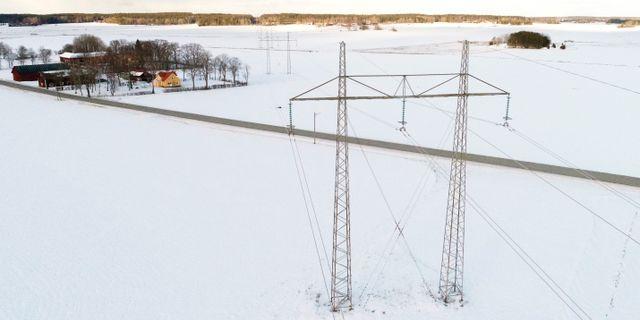 Kraftledningar med hus i bakgrunden i vinterlandskap. Fredrik Sandberg/TT / TT NYHETSBYRÅN