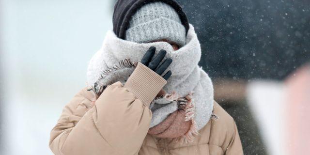En person täcker ansiktet från snövädret/arkivbild.  Charles Rex Arbogast / TT NYHETSBYRÅN