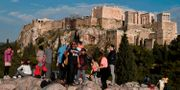Turister tar bilder nedanför Akropolis sedan turistmålet stängt till följd av ett blixtnedslag. LOUISA GOULIAMAKI / AFP