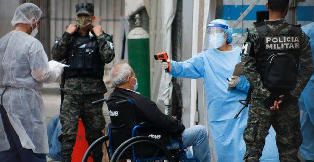 Sjukvårdspersonal tar tempen på en man i rullstol i Honduras. Elmer Martinez / TT NYHETSBYRÅN