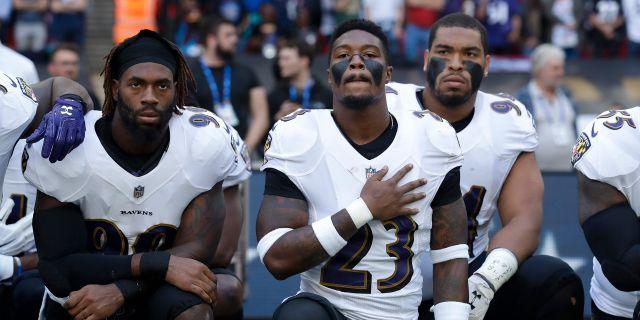 Baltimore Ravens-spelare knäböjer under nationalsången på söndagen. Matt Dunham / TT / NTB Scanpix